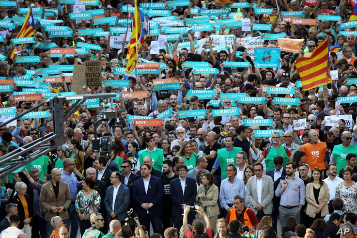 Catalan President Carles Puigdemont, front raw, center, takes part at a march to protest against the National Court's decision to imprison civil society leaders, in Barcelona, Spain, Saturday, Oct. 21, 2017.