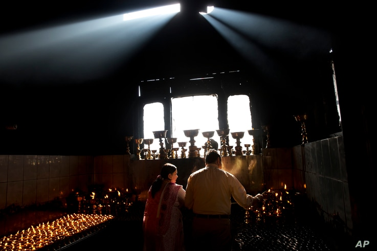 A Nepalese Buddhist couple light candles at the Boudhanath Stupa during Buddha Jayanti, or Buddha Purnima, festival in Kathmandu, Nepal, Monday, May 4, 2015. Hundreds of people have visited Buddhists shrines and monasteries in Nepal's quake-wracked...