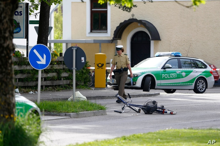 Police officers pass by a restaurant outside the station in Grafing near Munich, Germany, Tuesday, May 10, 2016.