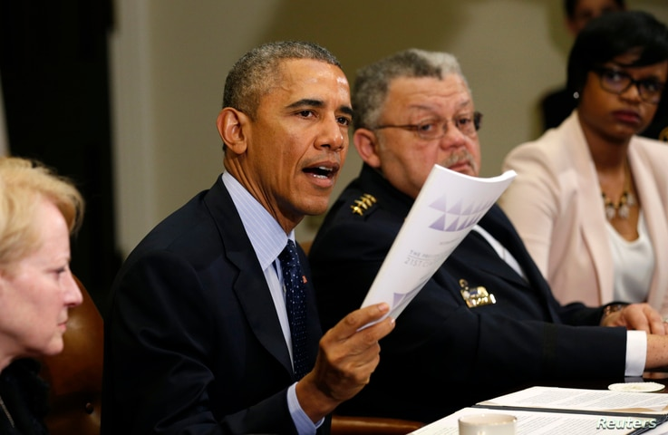 FILE - U.S. President Barack Obama holds up a copy of the report by the Task Force on 21st Century Policing at the White House in Washington, March 2, 2015. Beside Obama at right is Philadelphia Police Commissioner Charles Ramsey.