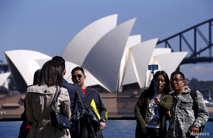 FILE - Chinese tourists taking pictures of themselves in front of the Sydney Opera House in Sydney, Australia, Sept. 28, 2015.