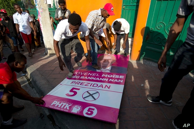 Supporters of presidential candidate Maryse Narcisse, from the Lavalas party, step on a campaign poster of presidential candidate Jovenel Moise, as they protest election results in Petion-Ville, Haiti, Nov. 12, 2015.
