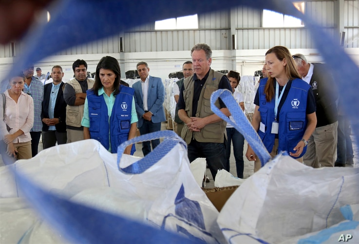 U.S. Ambassador to the United Nations Nikki Haley, center left, and World Food Program director David Beasely, center inspects a food pallet to be air-dropped deep inside Syria, in Amman, Jordan, May 21, 2017.
