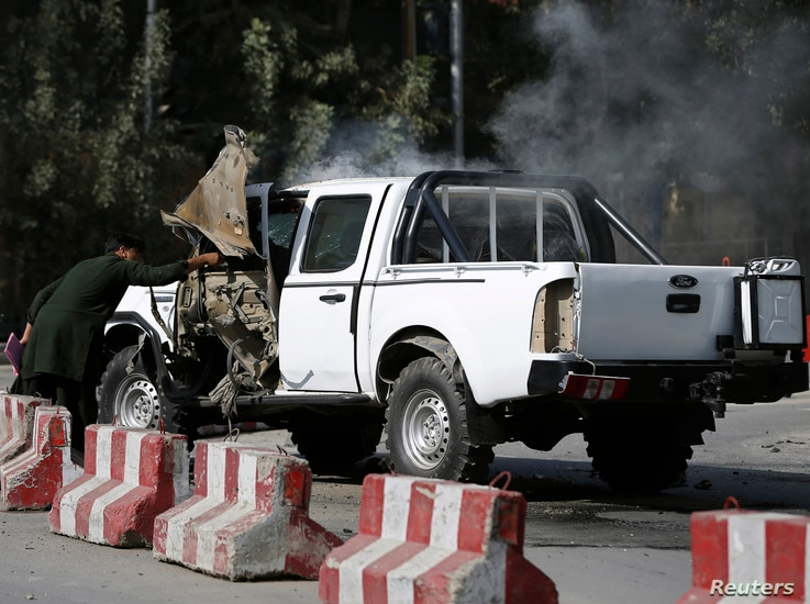 An Afghan plainclothes policeman inspects a military vehicle that was hit by a magnetic bomb in Kabul, Sept. 28, 2014.