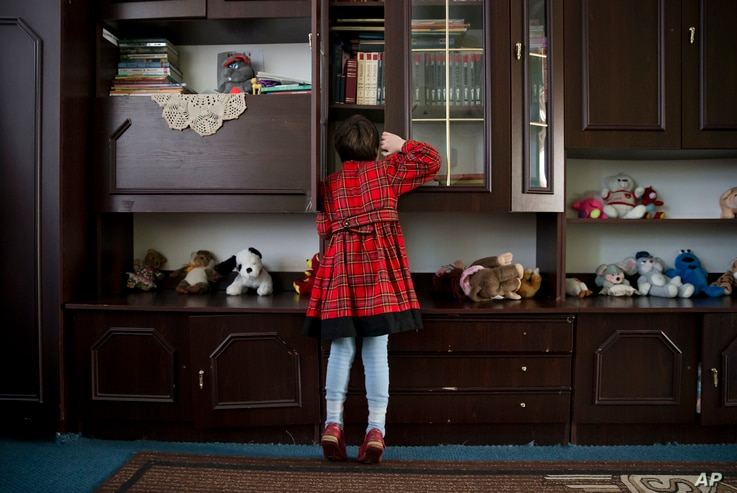 Veronika peers into a cupboard at a children's home in Khartsyzk, Ukraine, March 7, 2015.