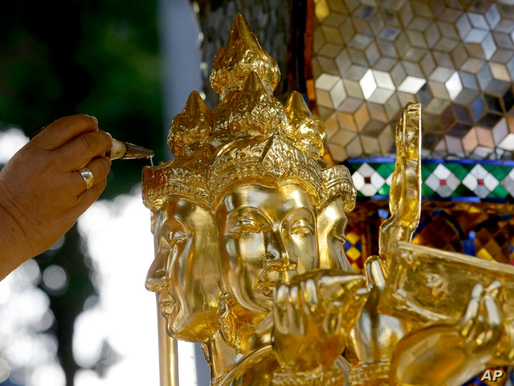 A Brahmin priest anoints Phra Phrom, the Thai interpretation of the Hindu god Brahma, with holy water during wellness and prosperity ceremony in Bangkok, Thailand, Friday, Sept. 4, 2015.
