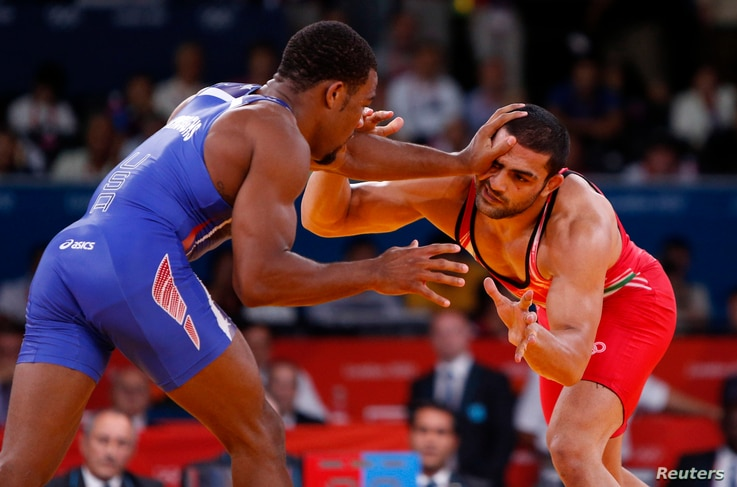 Jordan Ernest Burroughs of US (in blue) fights with Iran's Sadegh Saeed Goudarzi at London Olympics August 10, 2012