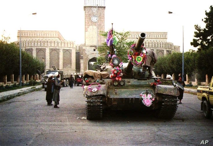 Tanks manned by Taliban fighters and decorated with flowers are shown in front of the the presidential palace, Sept. 27, 1996, in Kabul.The Islamic rebels pursued government forces Sept. 28 retreating from the devastated capital and said they had han...
