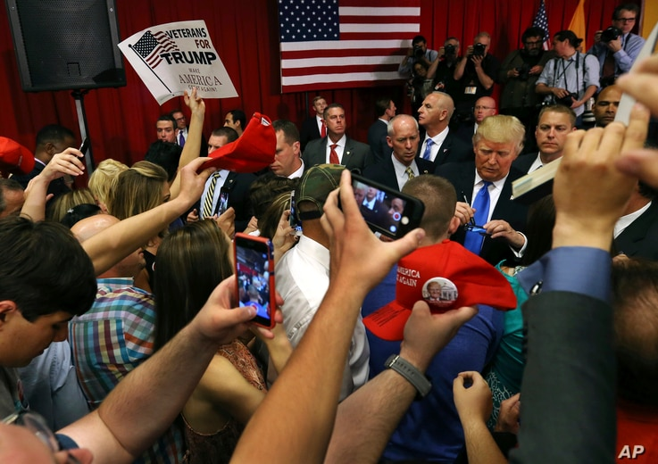 Supporters wave signs as Republican presidential candidate Donald Trump, center right, signs autographs for supporters after speaking at a campaign event Thursday, May 19, 2016, in Lawrenceville, N.J