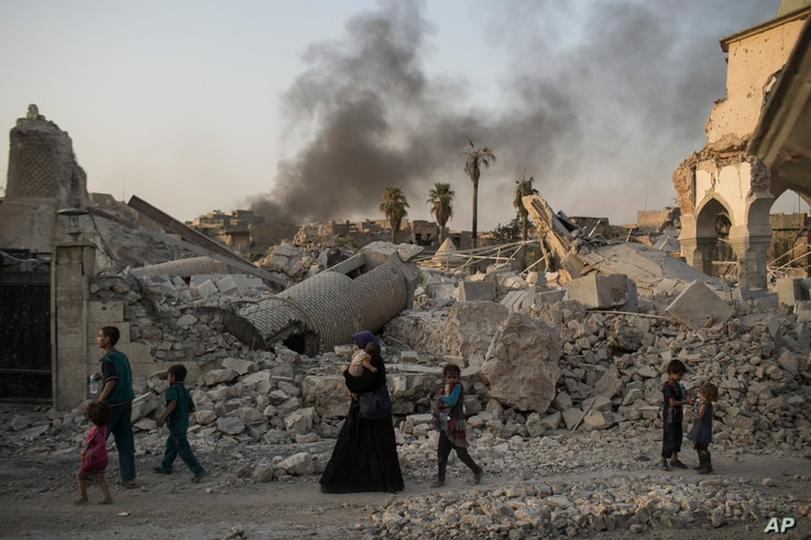 FILE - Iraqi civilians are seen walking past the destroyed al-Nuri mosque in the Old City of Mosul, Iraq, July 4, 2017.