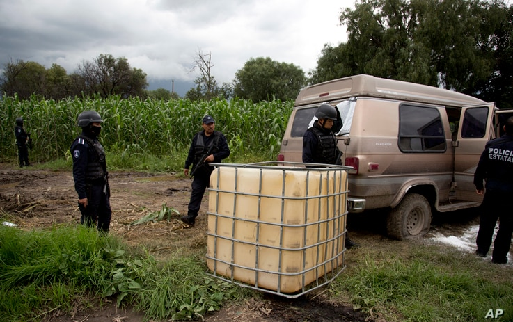 State police seize an abandoned truck that was used to carry stolen gasoline in plastic tanks, near an illegal tap into a state-owned pipeline in the middle of a cornfield in San Bartolome Hueyapan, Tepeaca, Mexico, July 11, 2017.