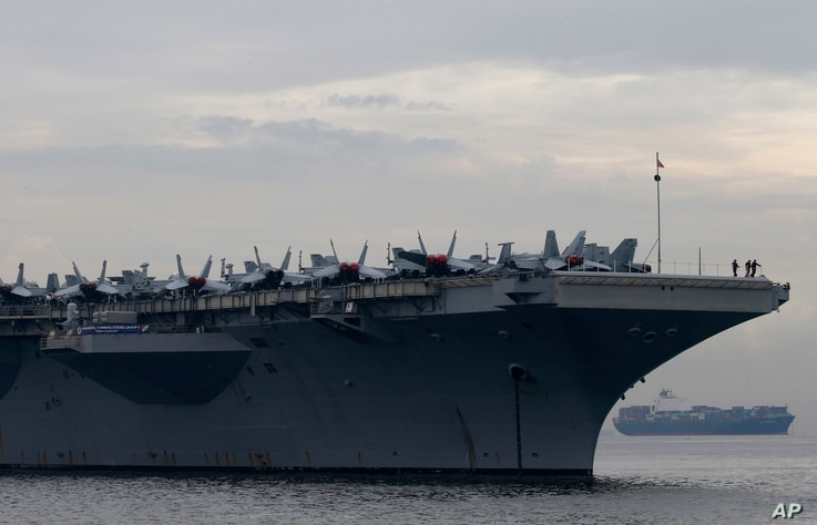 Sailors and fighter jets are seen on the deck of the U.S. aircraft carrier USS Ronald Reagan (CVN 76) as it anchors off Manila Bay for a goodwill visit, June 26, 2018, west of Manila, Philippines.