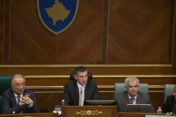 Speaker of the parliament Kadri Veseli, center, addresses Kosovo lawmakers during a debate, Aug. 3, 2015, on constitutional amendments that would allow the establishment of a special court to prosecute its top leaders and former guerrilla fighters fo...