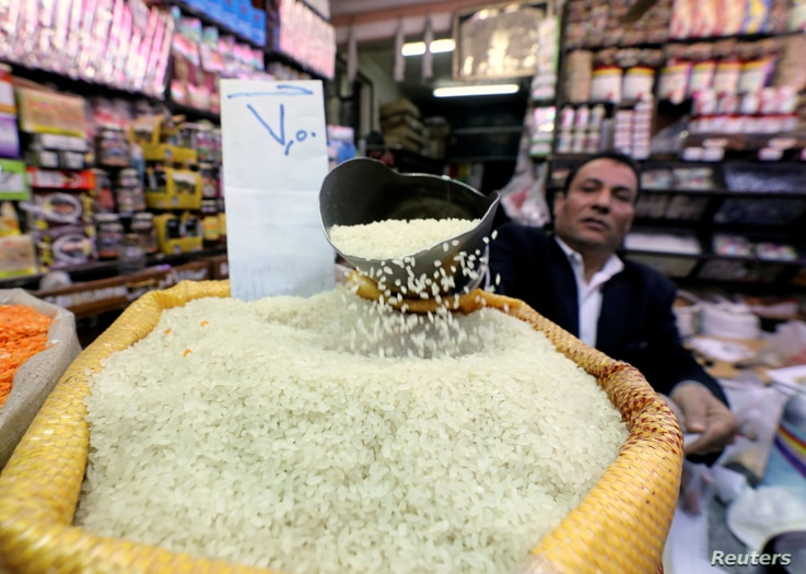 An Egyptian seller shows consumer goods as rice, at a vegetable market in Cairo, Egypt January 10, 2017.
