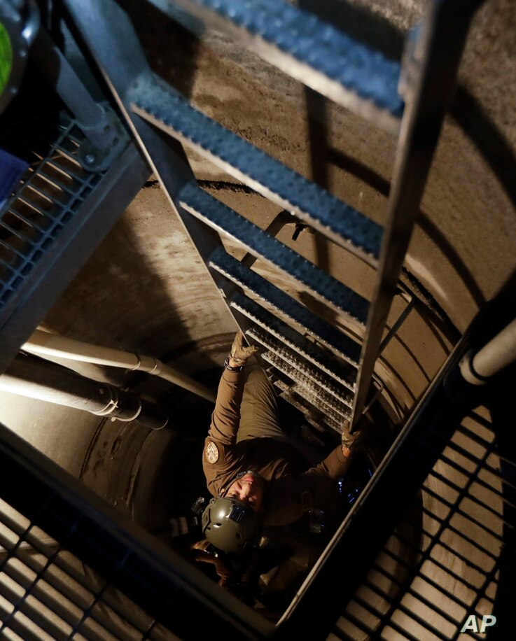 A U.S. Border Patrol agent climbs out of an entrance carved by the agency into a tunnel linking Tijuana, Mexico, and the entrance site in San Diego, Calif., March 6, 2017.