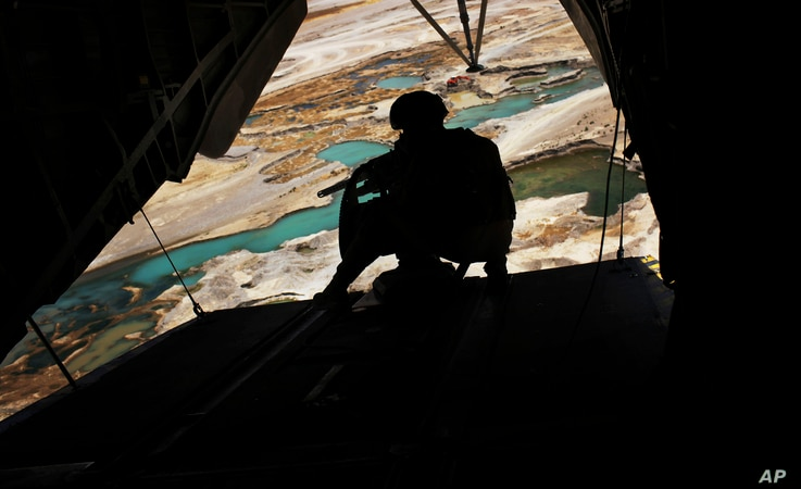 FILE - A U.S. Marine helicopter door gunner holds a heavy machine gun during a flight over Nimroz province on the border with the volatile Helmand province in southern Afghanistan.