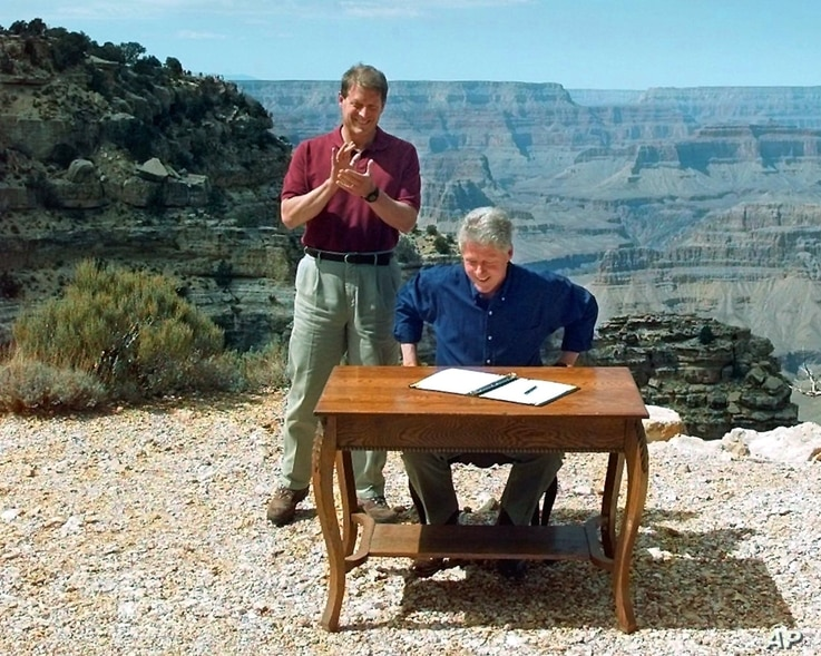 FILE - In this Sept. 18, 1996, photo, Vice President Al Gore applauds after President Bill Clinton signs a bill designating about 1.7 million acres of land in southern Utah's red-rock cliff as the Grand Staircase-Escalante National Monument, at the G...