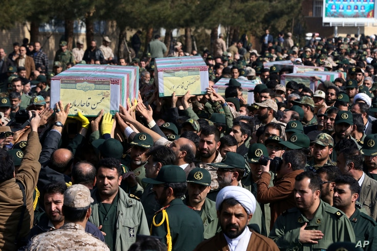 Civilians and armed forces members carry the flag-draped coffins of Iranian Revolutionary Guard's Gen. Mohsen Ghajarian, left, and some of his comrades who were killed in fighting in Syria, during their funeral ceremony in Tehran, Iran, Feb. 6, 2016....