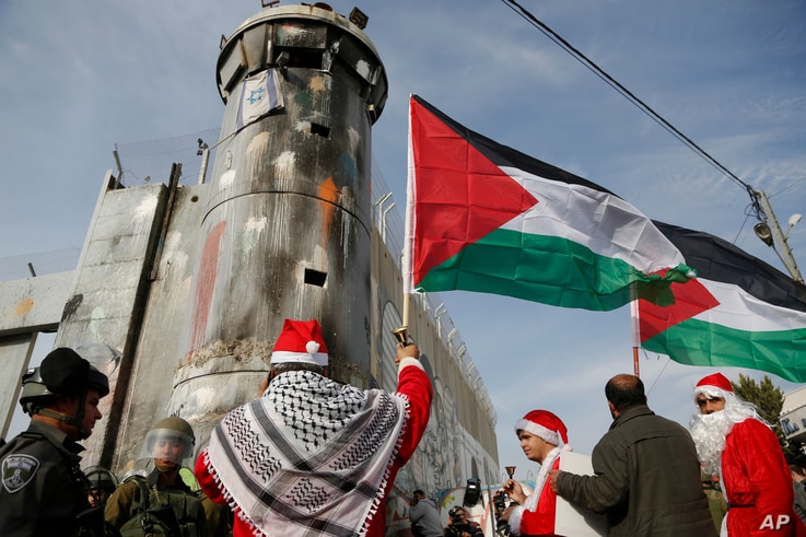 Palestinians dressed as Santa Claus confront Israeli border police during a protest in the West Bank city of Bethlehem, Dec. 23, 2017.