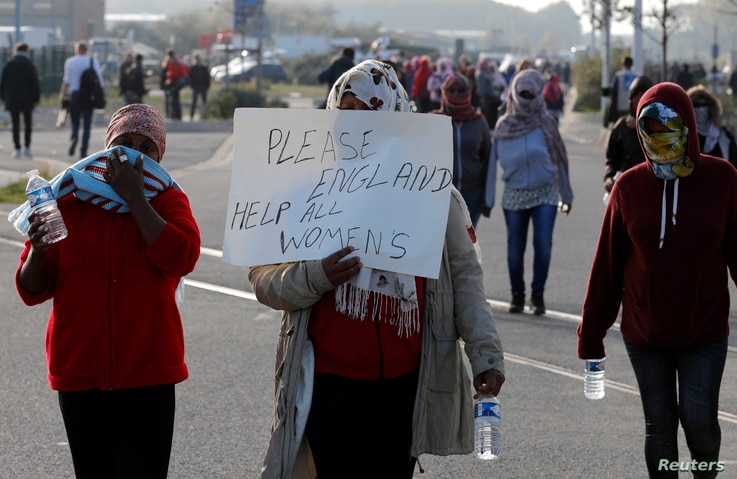 """Migrant women demonstrate on the second day of their evacuation and transfer to reception centers in France, as part of the dismantlement of the camp called """"the jungle"""" in Calais, France, Oct. 25, 2016."""