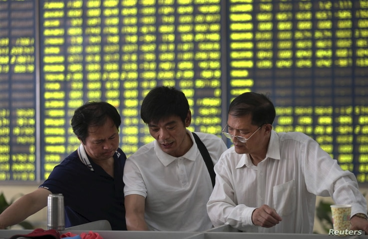 Investors talk in front of an electronic board showing stock information, filled with green figures indicating falling prices, at a brokerage house in Nantong, Jiangsu province, China, July 3, 2015.