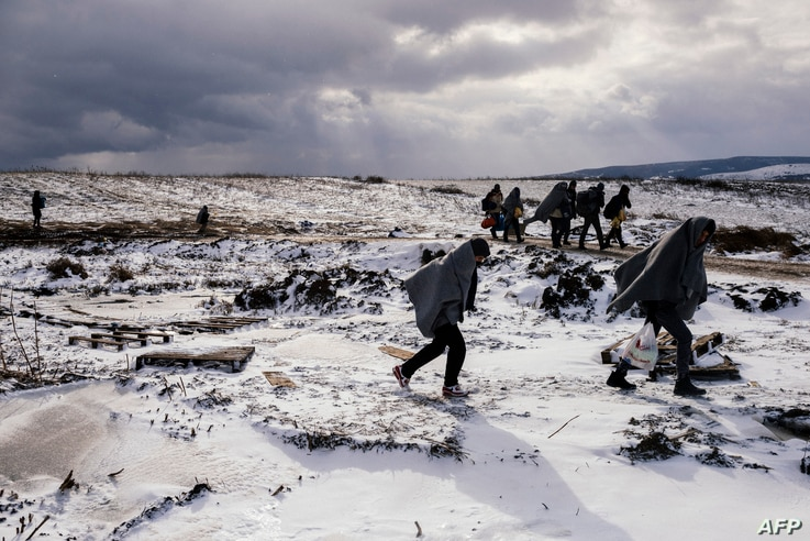 Migrants and refugees use their sleeping blankets to keep warm as they walk along snow covered fields after crossing the Macedonian border into Serbia, near the village of Miratovac, on January 18, 2016.
