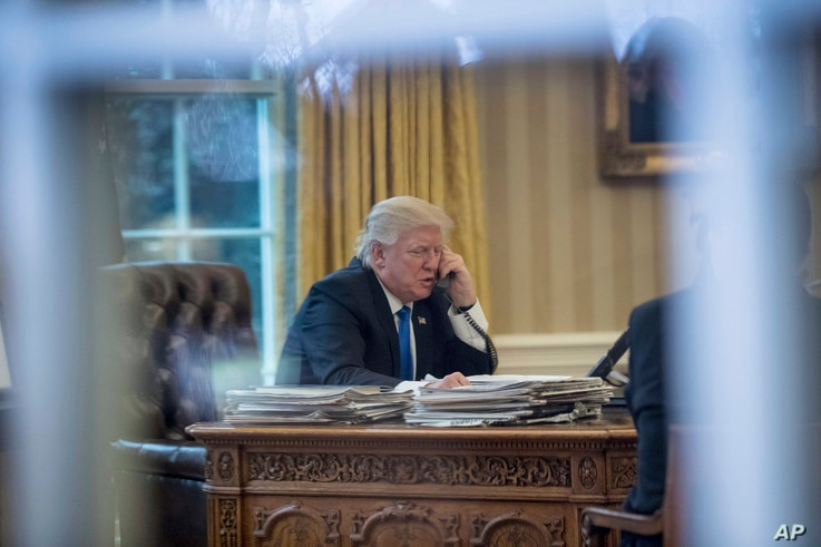 President Donald Trump speaks on the phone in the Oval Office at the White House in Washington, Jan. 28, 2017.