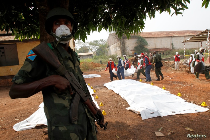 An African peacekeeping soldier stands guard as Red Cross workers move bodies from a mass grave at a military camp in Bangui, Feb. 17, 2014.
