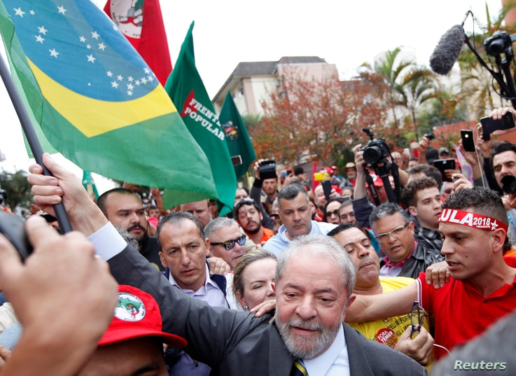 Former Brazilian President Luiz Inacio Lula da Silva carries a Brazilian flag as he arrives at Federal Justice, for a testimony in Curitiba, Brazil, May 10, 2017.