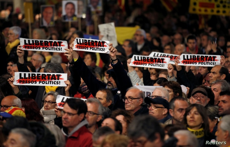 """People protest against the Supreme Court at Catalunya Square in Barcelona, Spain, Feb. 12, 2019.  Signs read, """"Freedom for political prisoners."""""""