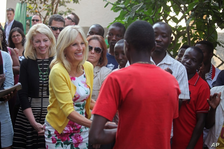 Jill Biden, second left, the wife of American Vice-President Joe Biden, shakes the hand of a former child soldier at a project that benefits from American Aid money in Bukavu, Democratic Republic of Congo, July 5, 2014.