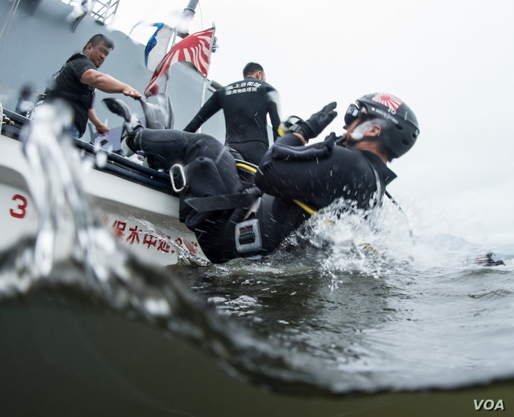 FILE - A Japan Maritime Self-Defense Force technician enters the water during a 2016 exercise with the Indian, Japanese and U.S. navies in the Indo-Asia-Pacific.