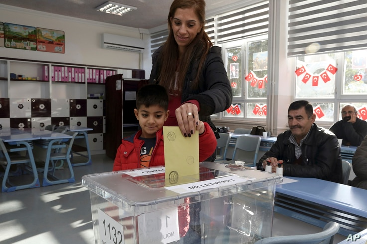 Arda Ozdemir, 7, casts his mother Kader Ozdemir's vote at a polling station at a primary school in Ankara, Nov. 1, 2015.