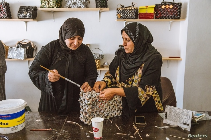 Syrian refugee Sahira Zoubi works on a new handbag, made from recycled newspapers, at an up-cycling workshop in Irbid city, northern Jordan, May 9, 2018.