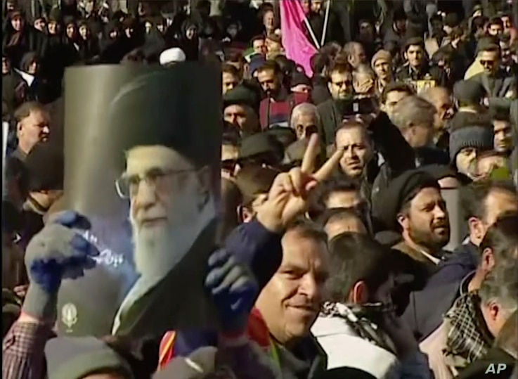 This frame grab from video provided by Iran Press, a pro-government news agency based in Beirut, shows pro-government demonstrators marching in, Arak, Iran, Jan. 3, 2018. Tens of thousands of Iranians took part in pro-government demonstrations in sev...
