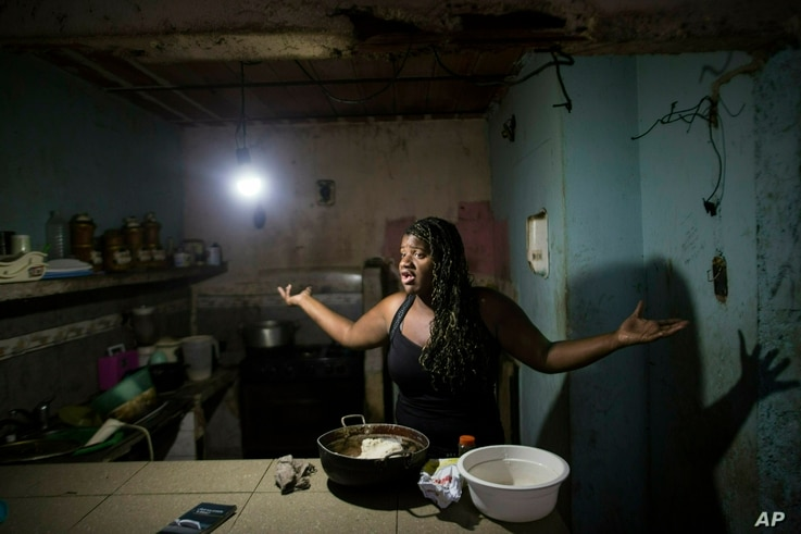 Dugleidi Salcedo complains to a neighbor about the high price of food as she prepares arepas for her three sons in her kitchen in the Petare slum, in Caracas, Feb. 14, 2019.