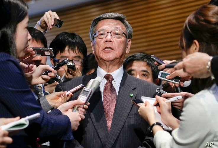 FILE - Okinawa Gov. Takeshi Onaga is surrounded by reporters after a meeting with Japanese Prime Minister Shinzo Abe at the latter's official residence in Tokyo.