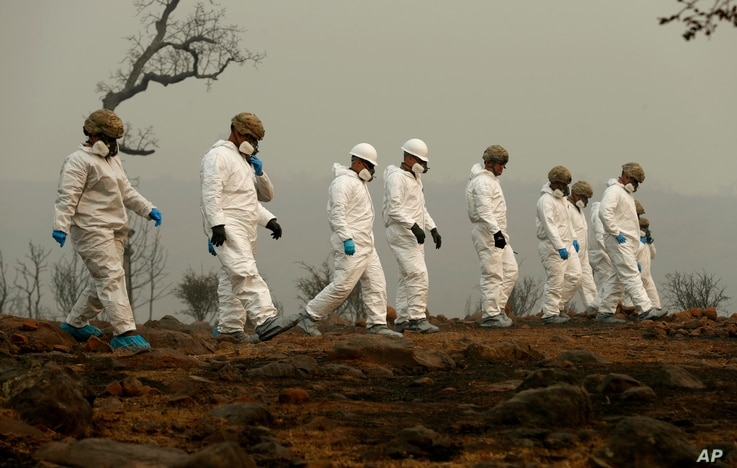 Members of the California Army National Guard search a property for human remains at the Camp fire, Nov. 14, 2018, in Paradise, Calif.