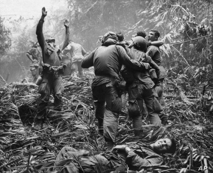 FILE - A photo shows the first sergeant of A Company, 101st Airborne Division, guiding a medevac helicopter through the jungle foliage to pick up casualties suffered during a five-day patrol near Hue, April 1968.