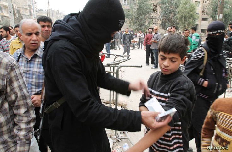 A fighter from the Islamist Syrian rebel group Jabhat al-Nusra searches a boy at the Karaj al-Hajez crossing in Aleppo, Nov. 7, 2013.