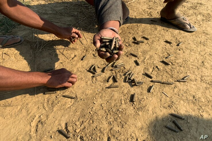FILE - Locals hold up bullet casings in a village in Rathedaung township, Rakhine state, after fighting between the Myanmar military and the Arakan Army, an ethnic Rakhine force, Jan. 28, 2019.