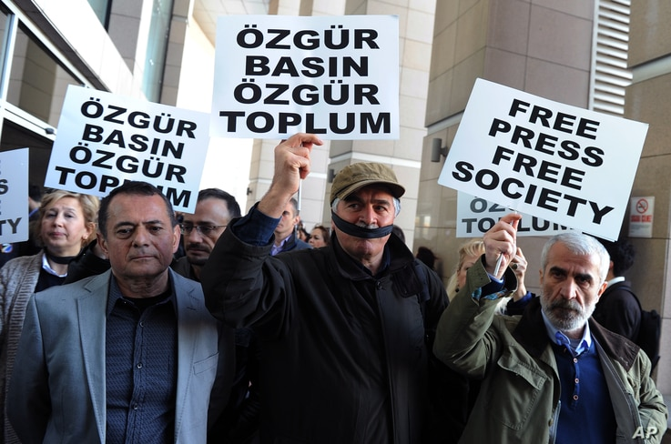 Turkish journalists cover their mouths with black ribbons before the trial of Can Dundar, the editor-in-chief of opposition newspaper Cumhuriyet and Erdem Gul, the paper's Ankara representative, outside the courthouse in Istanbul, April 1, 2016.