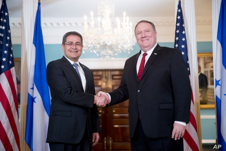 Secretary of State Mike Pompeo, right, shakes hands with Honduran President Juan Orlando Hernandez, left, at the State Department in Washington, June 18, 2018.