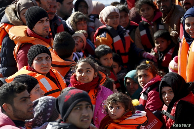 Refugees and migrants are seen on a dinghy as they approach the Ayios Efstratios Coast Guard vessel, during a rescue operation in the open sea between the Turkish coast and the Greek island of Lesbos, Feb. 8, 2016.