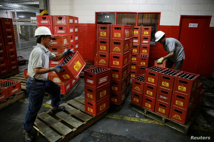 Employees carry beer boxes at a Regional warehouse in Caracas, Venezuela November 22, 2016.