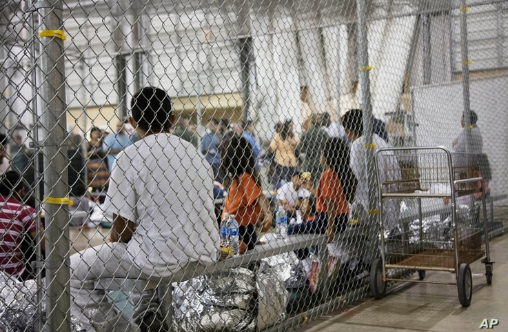 FILE - In this June 17, 2018 file photo provided by U.S. Customs and Border Protection, people who've been taken into custody related to cases of illegal entry into the United States sit in one of the cages at a facility in McAllen, Texas.