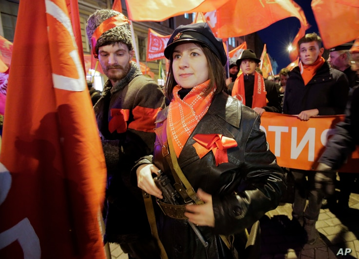 Communist Party supporters wearing Revolution ages uniform attend a rally to mark the 100th anniversary of the 1917 Bolshevik revolution in St. Petersburg, Russia, Nov. 7, 2017.