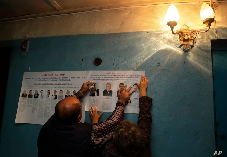 Election officials place pre-election leaflets at a polling station ahead of parliamentary elections in the village of Gusino, outside Smolensk, western Russia, Sept. 17, 2016.