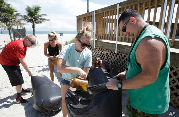 Kristen Allen, center front, and Travis Scott, right, fill bags with sand to prevent flooding to a nearby gift shop as they prepare for Hurricane Matthew, Oct. 5, 2016, in Cocoa Beach, Fla.