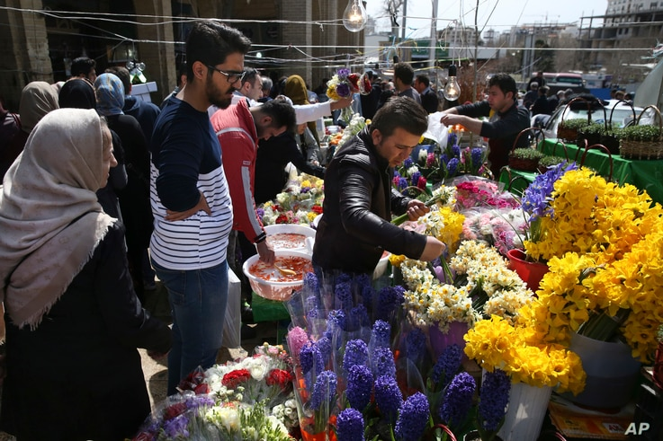 """A flower seller picks flower for his customer at Tajrish traditional bazaar in northern Tehran, Iran, ahead of the Iranian New Year, or Nowruz, meaning """"new day,"""" March 18, 2017."""